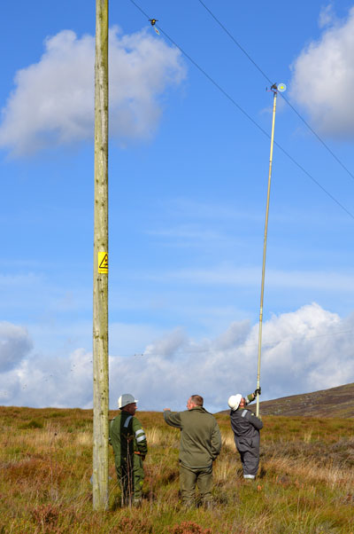 Scottish Power crew and Simon Lester fitting line markers to power lines at Langholm.